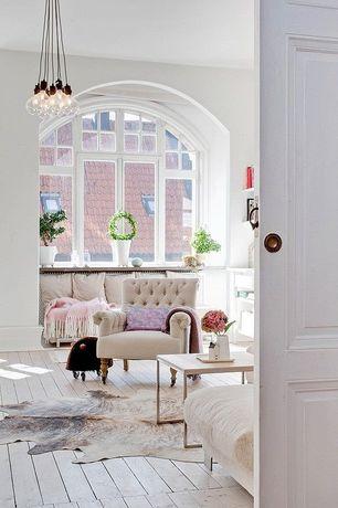 Traditional Living Room with Window seat, Safavieh Cow Hide Black/Brown Rug, Hardwood floors, Arched window, Chandelier