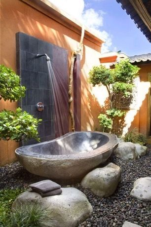 Asian Master Bathroom with exterior stone floors, Outdoor shower, Gravel landscape, D'vontz etna natural stone bathtub