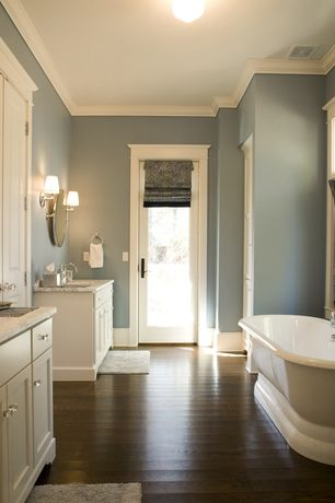 room with Dark hardwood floors, White painted cabinet finish, Wall sconce, Simple marble counters, Freestanding bathtub