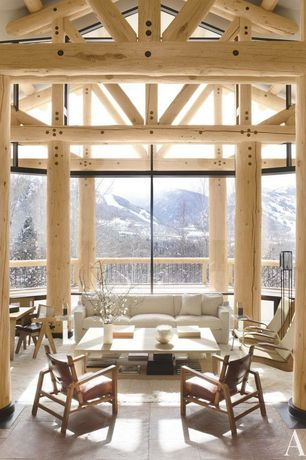 Rustic Great Room with Columns, Exposed beam, Henry Sofa, Log trusses, travertine floors, picture window, Natural light
