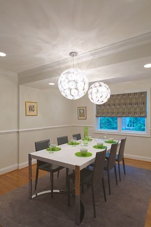 Modern Dining Room with Chair rail, Hardwood floors, Chandelier, Crown molding