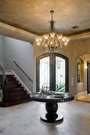 Mediterranean Entryway with Corner stairs, Arched entrance, Trey ceiling, stone tile floors, Wall sconce, Open archway