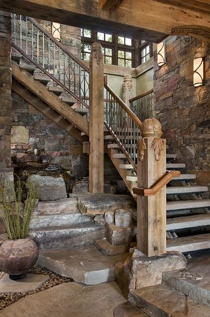 Rustic Staircase with Natural stone landing, slate floors, Wall sconce, Exposed beam, High ceiling, Interior stone wall