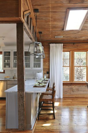 Cottage Dining Room with Glass panel cabinets, Exposed wood wall, Hardwood floors, Skylight, Pendant light, Marble countertop