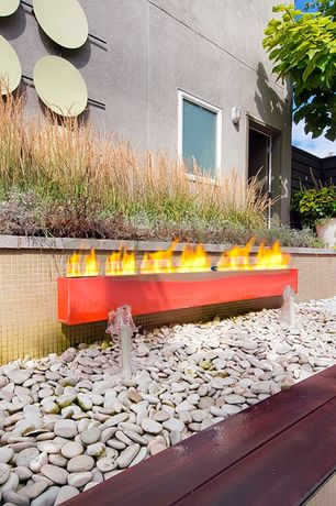 Modern Landscape/Yard with Fire pit, Fountain, Rain Forest Mexican Beach Pebble, Fence