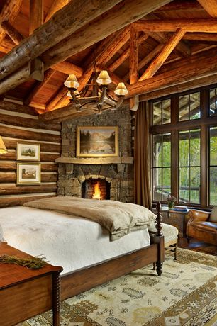Rustic Master Bedroom with Chandelier, stone fireplace, Hardwood floors, Standard height, Exposed beam, picture window