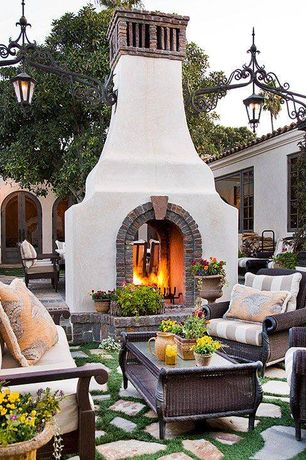 Mediterranean Patio with French doors, exterior stone floors, Outdoor wicker furniture, Freestanding fireplace, Pathway
