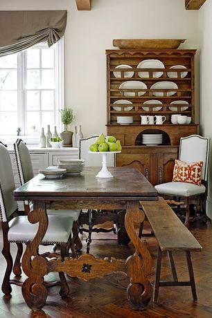 Traditional Dining Room with Herringbone hardwood floor, Hardwood floors, Paint, Built-in bookshelf, picture window