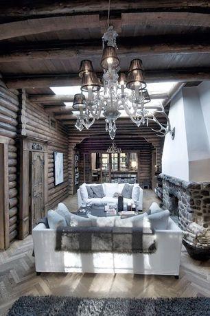 Eclectic Living Room with Skylight, stone fireplace, Hardwood floors, Chandelier, Exposed beam, Chevron wood floor pattern