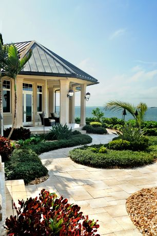 Tropical Landscape/Yard with Transom window, exterior stone floors, French doors
