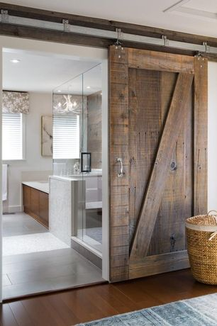 Modern Full Bathroom with Daltile First Snow Elegance 1 x1 Mosaic Honed, limestone tile floors, Hardwood floors, Barn door