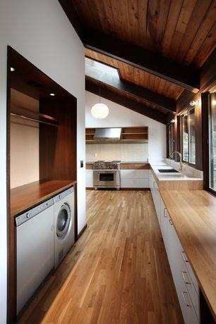 "Modern Laundry Room with Corian- Designer White, Quartz countertop, Wolf 36"" Gas Range, Hardwood floors, Exposed beam"