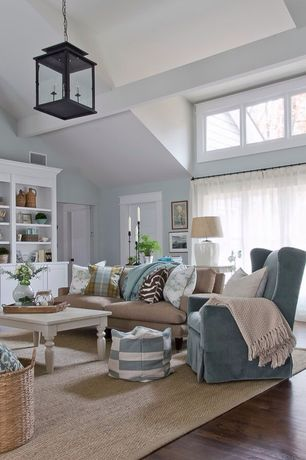 Cottage Living Room with Calisse 4-light lantern, Upholstered wingback chair, Built-in bookshelf, High ceiling, Exposed beam