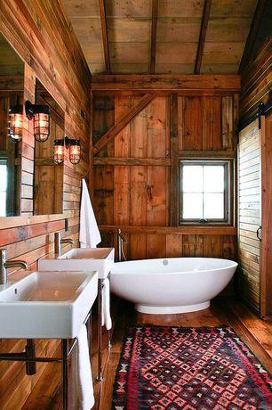 Rustic Master Bathroom with Casement, specialty door, Freestanding, Hardwood floors, Bathtub, Console sink, Sliding barn door