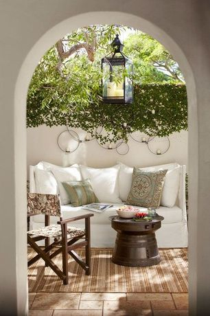 Mediterranean Patio with exterior stone floors, Fence, Arched doorway, Outdoor seating