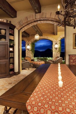 Mediterranean Dining Room with pocket door, Exposed beam, specialty door, Chandelier, Indoor/outdoor living, interior brick