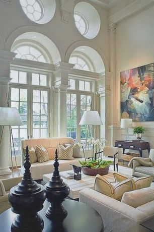 Traditional Living Room with Columns, Hardwood floors, Arched window, Wainscotting, Crown molding, French doors, High ceiling