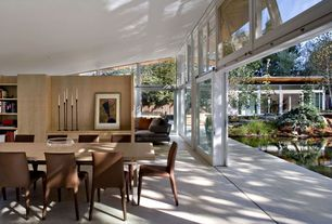 Contemporary Dining Room with Garage door stylr patio door, Built-in bookshelf, Concrete floors, High ceiling
