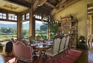 Country Dining Room with Hardwood floors, Chandelier, Exposed beam, picture window, Wall sconce, Cathedral ceiling