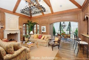 Mediterranean Living Room with Arched window, Chandelier, Hardwood floors, High ceiling, Wall sconce, Casement, Exposed beam