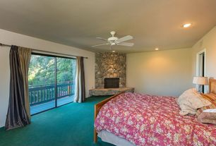 Traditional Guest Bedroom with Standard height, can lights, Carpet, Ceiling fan, sliding glass door, stone fireplace