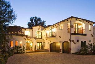 Mediterranean Exterior of Home with Fence, Arched window, Pavers, French doors