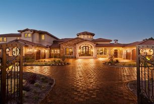 Mediterranean Exterior of Home with Entrance gate, exterior interlocking pavers, Arched doorway