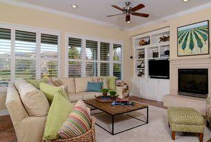 Cottage Living Room with Crown molding, travertine tile floors, Built-in bookshelf, Ceiling fan