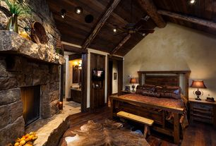 Rustic Master Bedroom with High ceiling, Hardwood floors, stone fireplace, flush light, Exposed beam, Ceiling fan