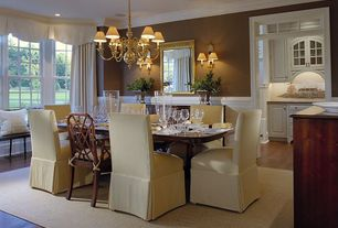 Traditional Dining Room with can lights, double-hung window, Transom window, Wall sconce, Crown molding, Wainscotting