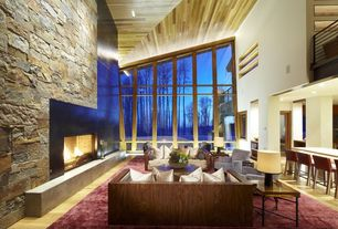 Modern Great Room with Floor to ceiling windows, can lights, Wood wrapped tuxedo sofa, Stacked stone wall, Concrete fireplace