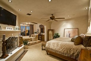 Mediterranean Guest Bedroom with Ceiling fan, Chandelier, Small crest flat guard fireplace screen, Carpet, Cement fireplace