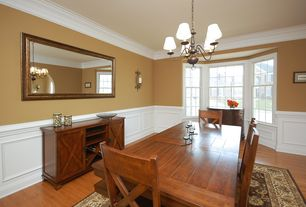 Traditional Dining Room with Wainscotting, Wall sconce, Chandelier, Crown molding, Hardwood floors, Chair rail
