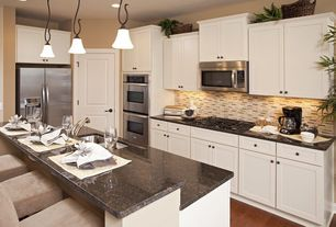 Traditional Kitchen with Flat panel cabinets, specialty door, Kitchen island, Simple granite counters, built-in microwave