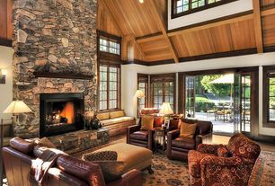 Rustic Living Room with Laminate floors, Skylight, Carpet, Cathedral ceiling, Exposed beam, French doors, stone fireplace