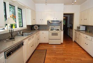 Cottage Kitchen with Hardwood floors, Track lighting, Corian, Flat panel cabinets, Oak hardwood flooring, Corian counters