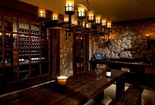 Rustic Wine Cellar with sandstone floors, Chandelier, Crown molding, Wall sconce, Built-in bookshelf