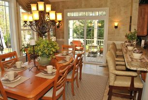 Traditional Dining Room with Breakfast bar, Complex granite counters, stone tile floors, Wall sconce, Chandelier, Casement