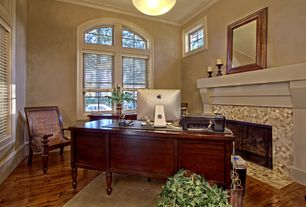Traditional Home Office with stone fireplace, Hardwood floors, Crown molding, Pendant light, Arched window