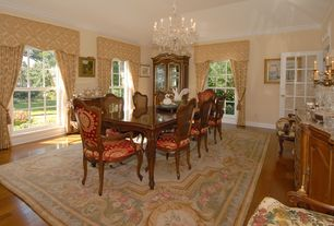 Traditional Dining Room with Crown molding, Chandelier, Glass panel door, High ceiling, Hardwood floors