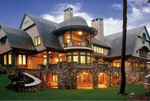 Country Exterior of Home with Curved balcony, Open archway, Wrap around porch, River rock, Columns