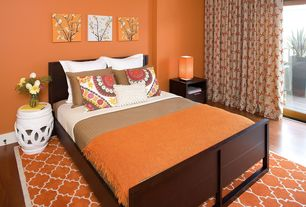 Contemporary Guest Bedroom with Mahogany bed, Orange area rug, Laminate floors, White ceramic end table