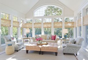 Traditional Living Room with Natural woven shades, Paintable white beadboard, Neutral area rug, Arched window, Sunroom