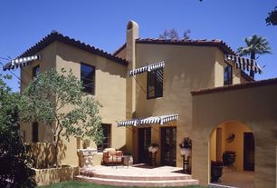Mediterranean Patio with exterior stone floors, French doors, exterior awning