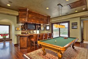 Craftsman Game Room with Built-in bookshelf, Standard height, Hardwood floors, Pendant light, sliding glass door, can lights