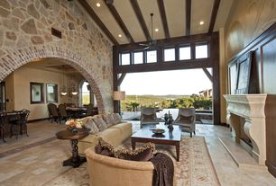 Mediterranean Living Room with Natural stone wall, Indoor/outdoor living, Paint, Fireplace, Exposed beam, stone tile floors