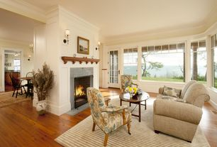Traditional Living Room with brick fireplace, Hardwood floors, Wall sconce, Crown molding, Standard height, French doors