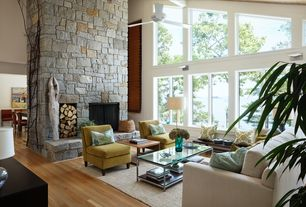 Contemporary Living Room with High ceiling, Exposed beam, Laminate floors, Wall sconce, Ceiling fan, stone fireplace