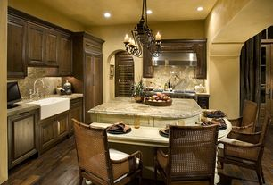 Mediterranean Kitchen with Wolfe - 6 burner + griddle, double oven, Kitchen island with seating, Hardwood floors