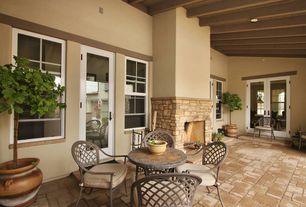 Mediterranean Patio with outdoor pizza oven, French doors, exterior brick floors